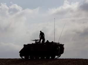 Israeli soldier stands on military vehicle near Gaza.