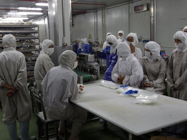 In this July 20, 2014 photo released by China's Xinhua News Agency, workers gather while they have nothing to do at the workshop of Shanghai Husi Food Co.