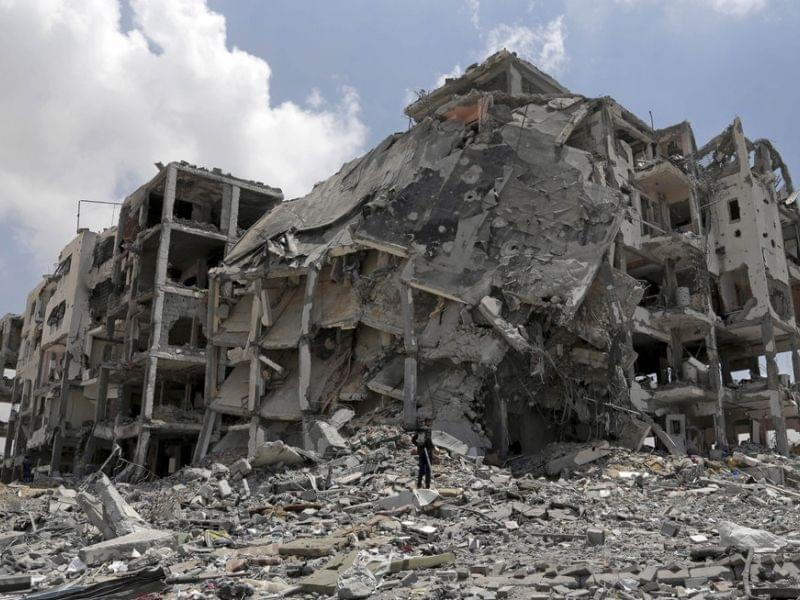 Palestinian searches for salvageable items in rubble