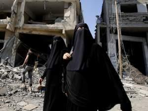 Palestinian women walk in Gaza City's Shijaiyah neighborhood