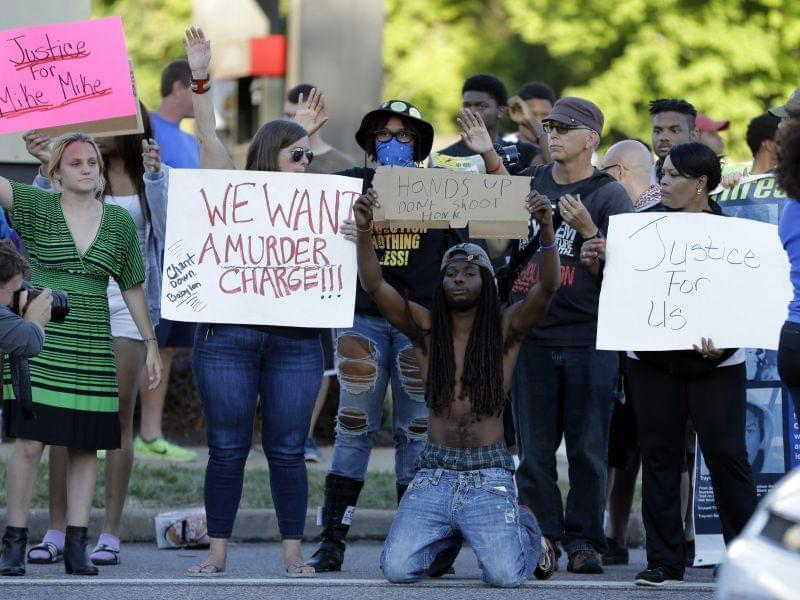 Protesters hold up signs along a road Tuesday, Aug. 12, 2014, in Ferguson, Mo. Racial tensions have run high in in the predominantly black city of Ferguson, following the shooting death by police of Michael Brown, 18, an unarmed black man.