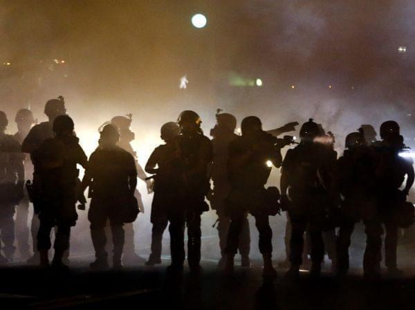 Police walk through a cloud of smoke, clashing with protesters in Ferguson, Mo. Wednesday night.