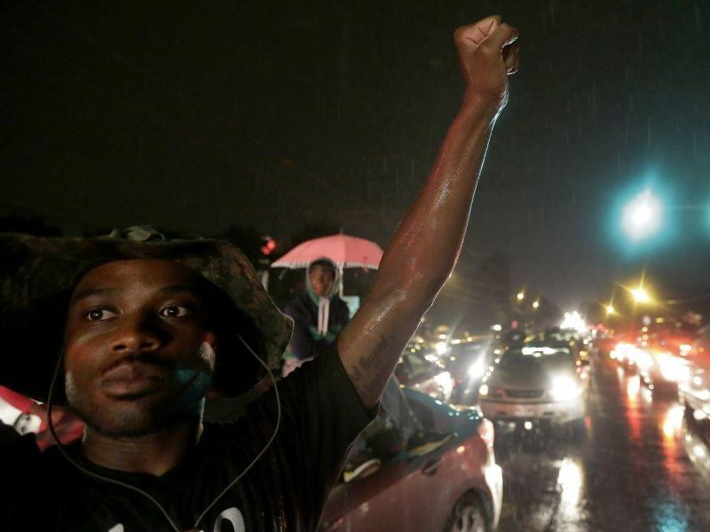 A protestor in front on a convenience store in Ferguson, Mo.