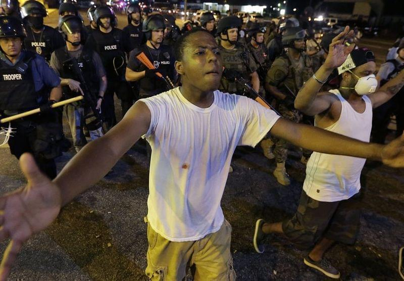 Protesters walk in a line in Ferguson, Mo.