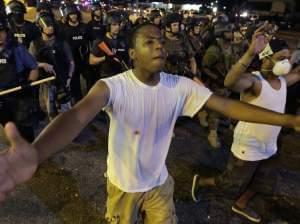 Protesters walk in a line in Ferguson, Mo.