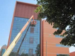Workers on a crane work on the outside of the new University of Illinois ECE building on its first day of hosting classes Monday.