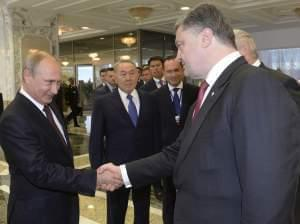 Vladimir Putinshakes hands with Ukrainian President Petro Poroshenko,after posing for a photo in Minsk, Belarus, August 26.