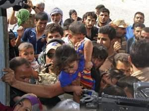People try to board an Iraqi helicopter bringing supplies in Amerli.