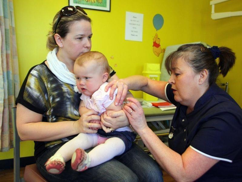 Helen Downs holds her 14-month old Amelia for an MMR shot in England in April 2013.