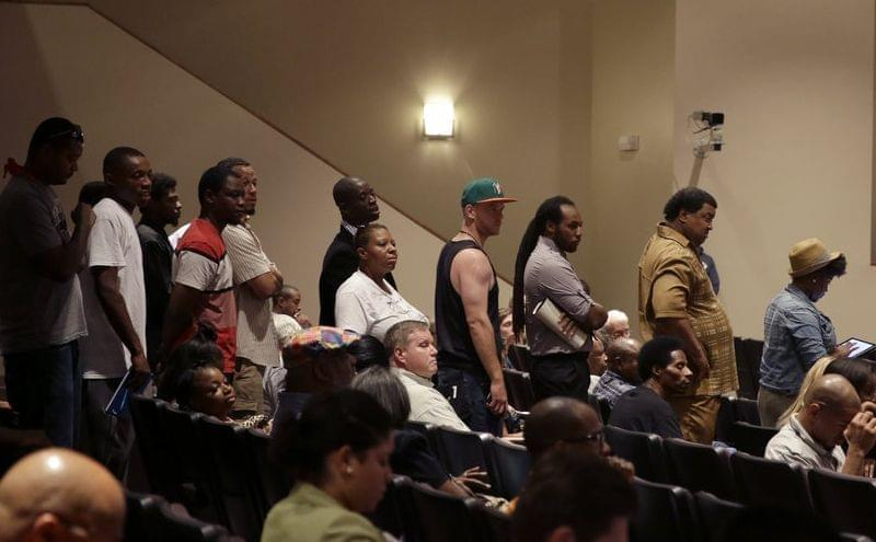 A line of people wait to speak during a meeting of the Ferguson City Council.