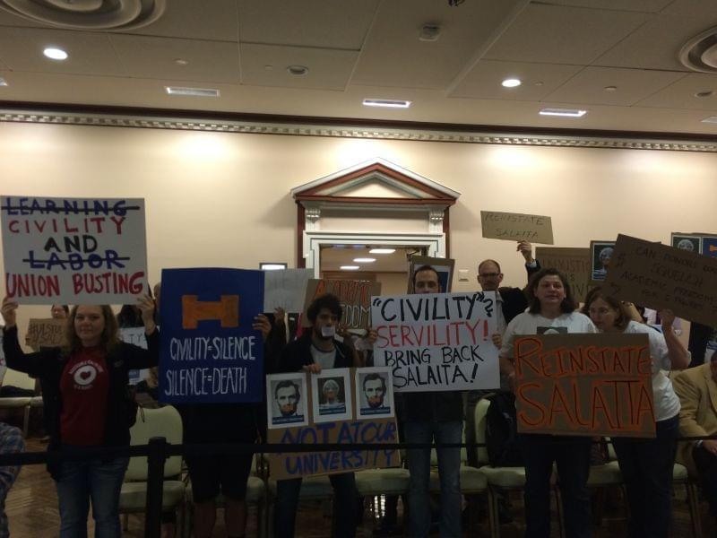 Backers of Steven Salaita carry signs, showing their support during the U of I Trustees meeting.