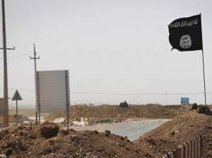 A flag of the Islamic State is seen on the other side of a barge in Iraq.