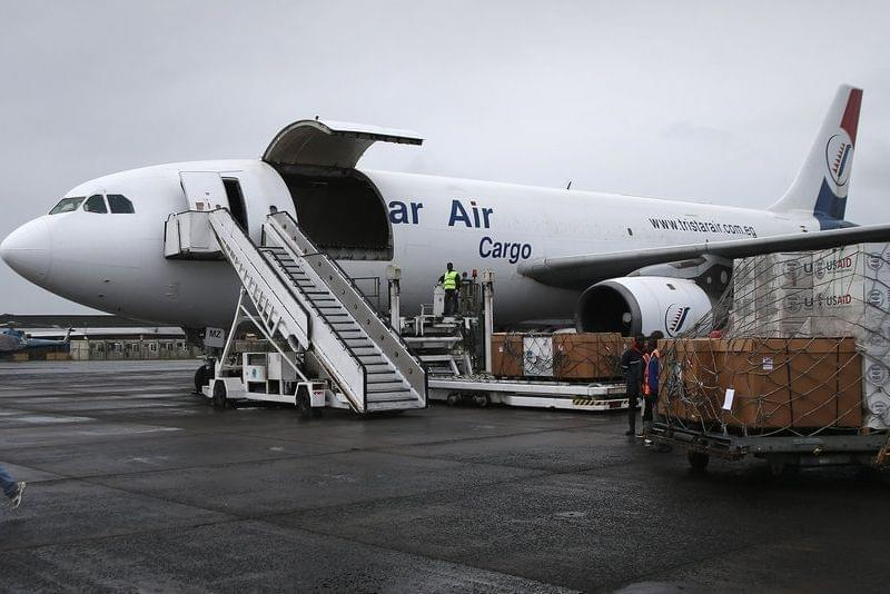 Workers unload medical supplies from a USAID cargo plans in Liberia in August.