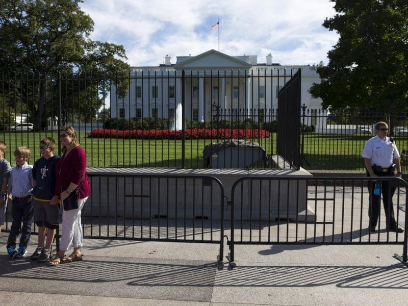 A Secret Service officer stands near tourists outside the White House Monday.