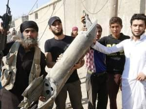 Islamic State militant stands next to Raggah residents on September 16th, holding wreckage of a Syrian war plane.