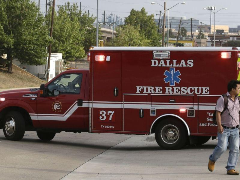 An ambulance pulls out for a run from a Dallas fire station. An EMT crew there is on a 21 day quarantine.