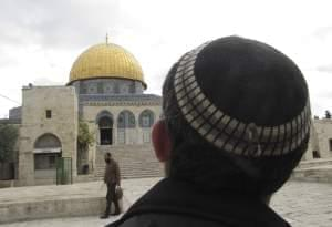 A Jewish man looks toward the Dome of the Rock as the Jerusalem site known by Jews as the Temple Mount, and by Muslims as the Noble Sanctuary.