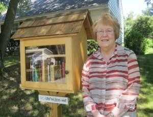 Judith Selle stands with her Little Free Library outside her home in Decatur.