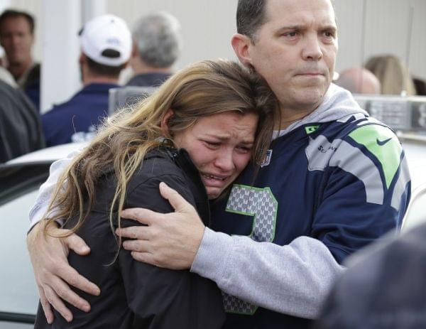 People react as they wait at a church where students were taken to meet with parents after a shooting in Marysville, Washington.