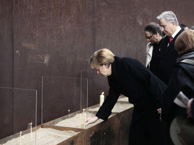 German Chancellor Angela Merkel and the Mayor of Berlin Klaus Wowereit place candles to commemorate victims at the Berlin Wall Memorial Site.