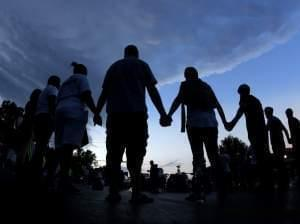 People stand in prayer August 20th in Ferguson August 20th.
