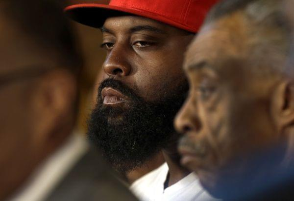Michael Brown Sr listens alongside Rev. Al Sharpton Tuesday in St. Louis County, Missouri.