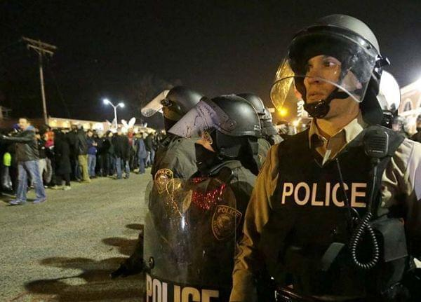 Police watch the protesters gather Tuesday in Ferguson.