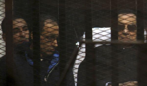 Mubarak lies on a gurney next to his son Gamal in the defendants cage, during a court hearing in Cairo