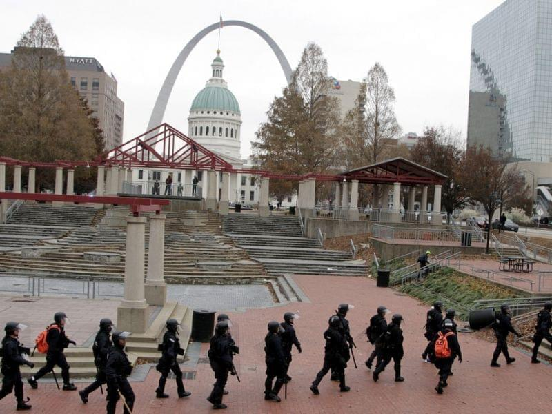 Officers wear riot gear walking through a park in downtown St. Louis.