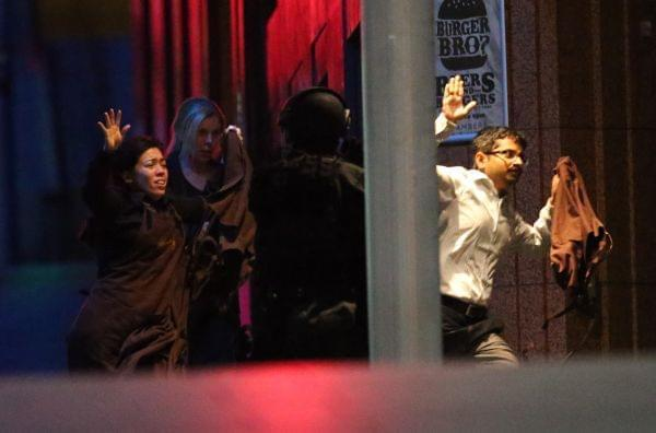 Hostages run to safety during a cafe siege in Sydney.