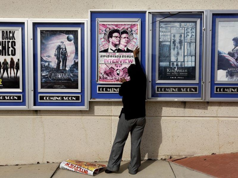 "A poster for ""The Interview"" is taken removed from a display case at a Carmike Theater in Atlanta."