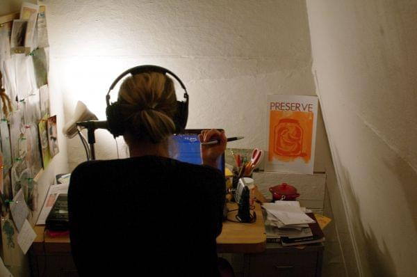 A woman recording audio in a small room