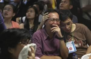 Relatives of passengers of the missing AirAsia flight react to news on television.