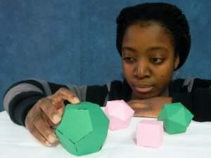 Student Sonie Toe examines polyhedra made from paper