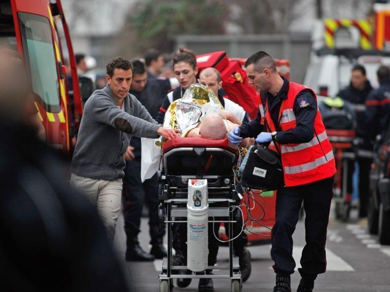 An injured person is transported to an ambulance after a shooting at a French satirical newspaper