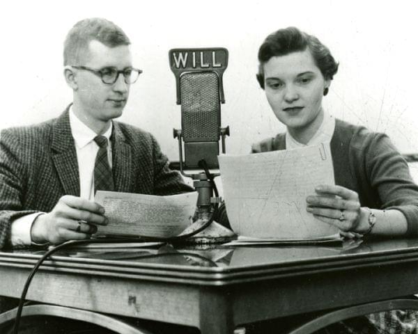 A man and a woman reading from scripts into a microphone with the WILL logo on it