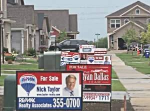Newly built houses in southwest Champaign with for sale signs in the front yard.