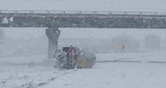 An overturned semi-tractor tanker trailer lies along I-57 in Champaign in snowy weather, following an accident.