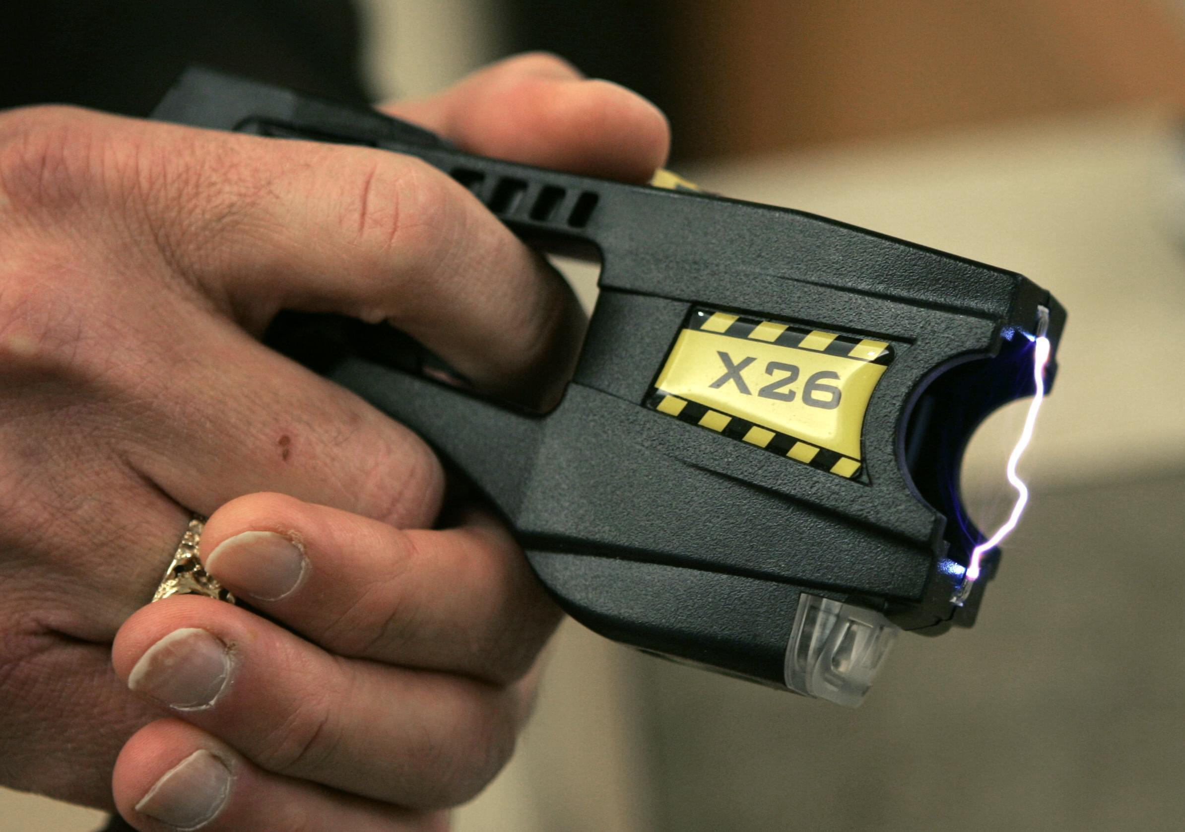A Taser X26 is shown on display.