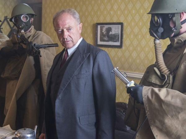 Foyle flanked by two gas-masked soldiers, pointing rifles at him.