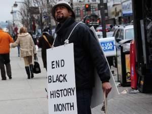 Filmmaker Shukree Tilghman wearing a protest sign in Harlem.