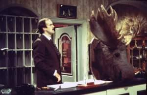 John Cleese behind a hotel desk, with a stuffed moose head nearby.