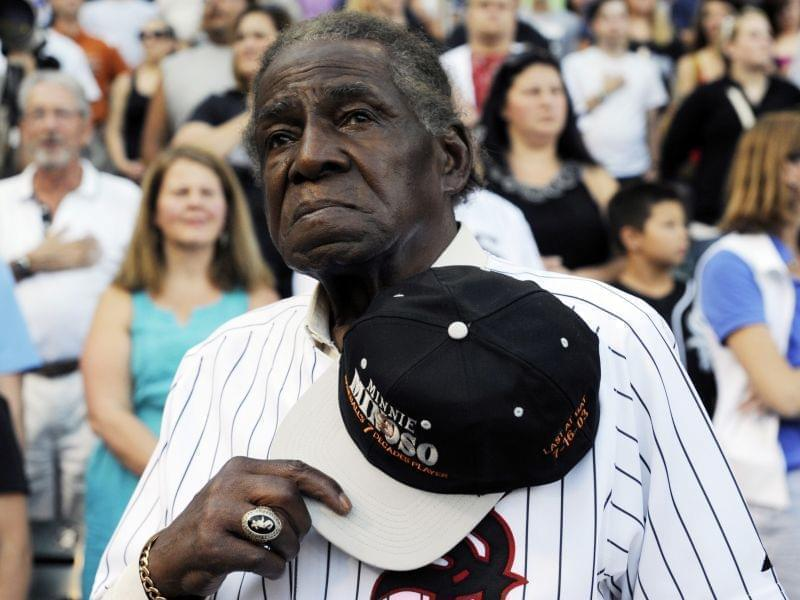 Former Negro Leaguer and Chicago White Sox player Minnie Minoso stands during the national anthem before a baseball game between the Chicago White Sox and the Texas Rangers in August 2013.