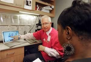 In this photo provided by College of American Pathologists, a pathologist explains a Pap test slide to Cassandra Ingram, 53, of Blaine, Minn. at North Point Health & Wellness Center's See, Test & Treat™ program Tuesday, Oct. 4, 201