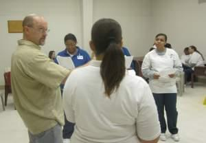 Millikin University Professor Alex Miller instructs women from the Decatur Correctional Center in a scene from Macbeth.