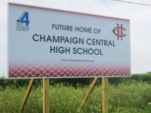 A sign at the proposed future site of Champaign Central High School stands in a field along Olympian Drive on the north edge of Champaign, with the Ashland Park residential subdivision visible in the distance.