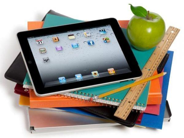 iPad tablet sitting on top of notebooks, with ruler and apple nearby