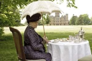 The Dowager Countess sits at a table on the lawn of Downton Abbey.