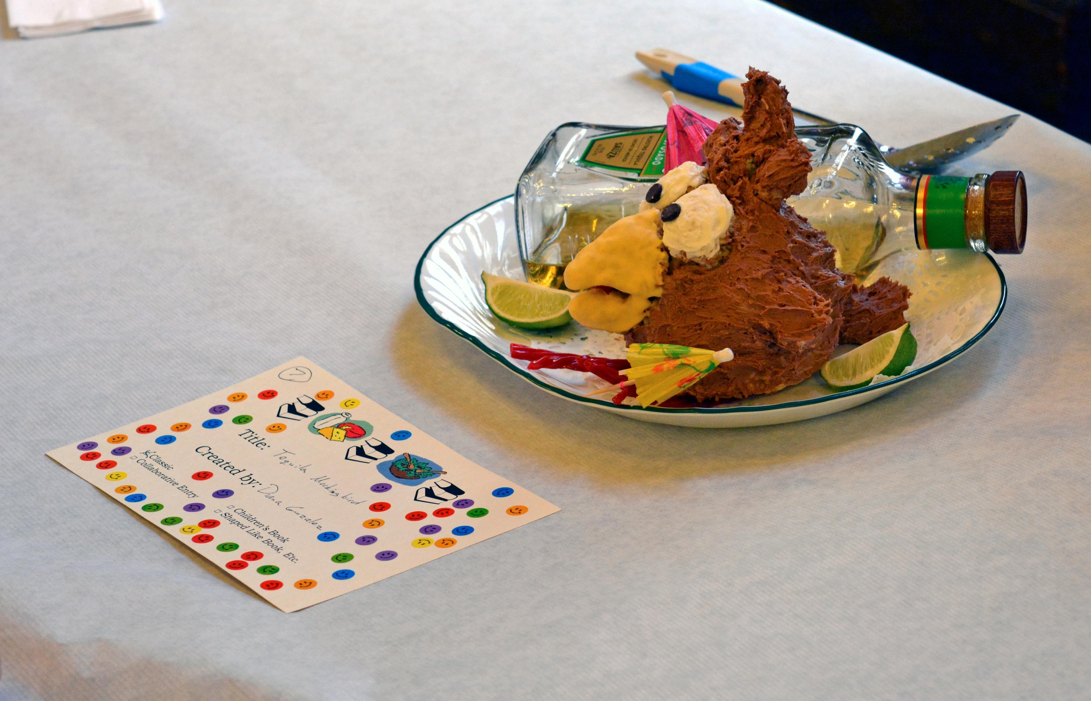 a cake called tequila mockingbird decorated to look like a drunk bird and a bottle of tequila