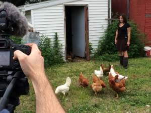 A woman stands outside with several chickens as she's having her photo taken.
